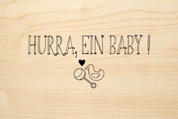 Holzgrusskarte - Geburt - Hurra, ein Baby. Ausgemaltes Herz, Rassel und Vogel abgebildet.
